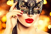 Beauty model woman wearing venetian masquerade carnival mask at party, over holiday dark background. Christmas and New Year celebration. Sexy girl with holiday makeup and manicure. Red lips and nails  poster