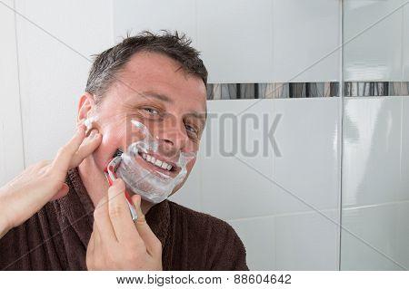 Man Shaving With A Razor Blade And Shaving Cream In Bathroom