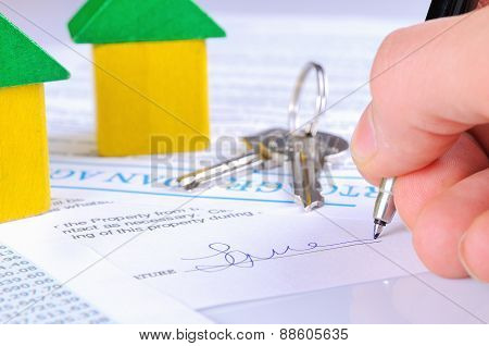 Signing The Mortgage Contract To Delivery Of Keys With Wooden Houses