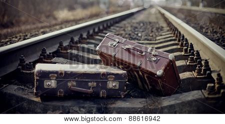Two Vintage Suitcases Thrown On Railway Rails.
