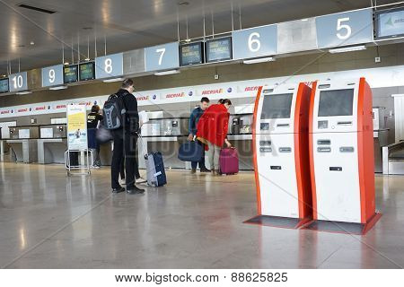 VALENCIA, SPAIN - APRIL 13, 2015: Airline passengers inside the Valencia Airport checking in at the Iberia counter. About 4.59 million passengers passed through the airport in 2013.