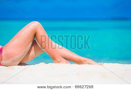 Female slim tanned legs on  white tropical beach poster