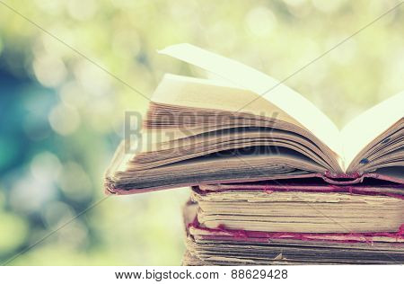 Close up on old book on colorful bokeh background - retro styled photo