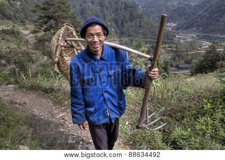 Asian Peasant Goes To Work In Fields With  Hoe Fork.