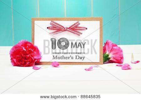 May 10th Mothers Day card with pink carnations over teal wooden background poster