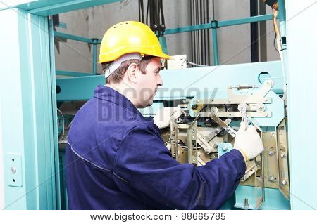 Male technician machinist worker at work adjusting elevator mechanism of lift with spanner