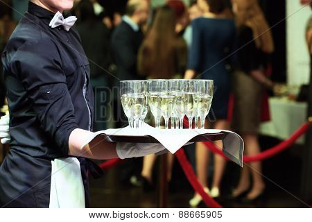 catering or celebration concept. Waiter holding a tray with glasses of vine at party