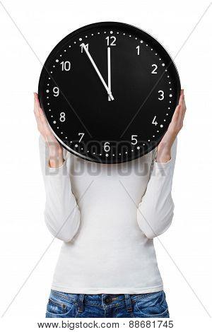 Woman holding a clock over face