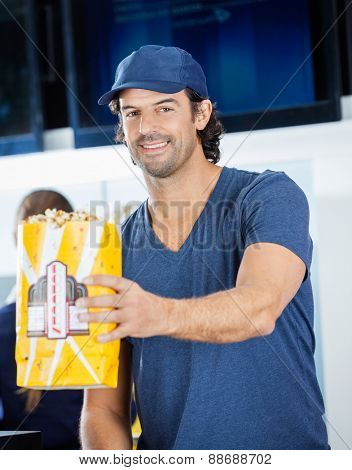 Portrait of smiling male worker offering popcorn paperbag at cinema concession stand