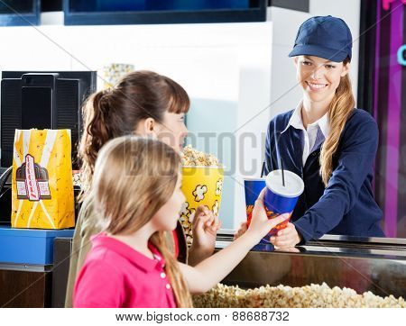 Sisters buying snacks from female concession worker at cinema counter