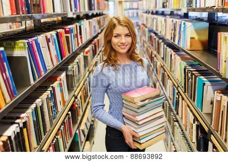 people, knowledge, education and school concept - happy student girl or young woman with book in library poster