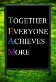 TOGETHER EVERYONE ACHIEVES MORE message on sidewalk blackboard sign against green grass background. Copy Space available. Concept image poster