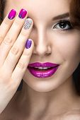 Beautiful girl with a bright evening make-up and purple manicure with rhinestones. Nail design. Beauty face. Picture taken in the studio on a black background. poster