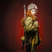 Historical reenactment of soviet union army by pretty girl with mosin-nagan in beautiful light on red background poster