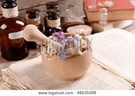 Old book with dry flowers in mortar and bottles on table close up