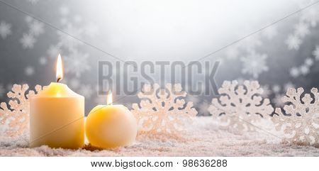 Christmas decoration,burning candles on snow.