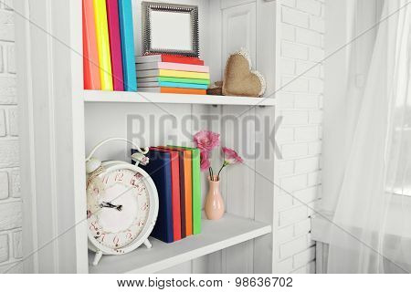 Books and decor on shelves in cupboard poster