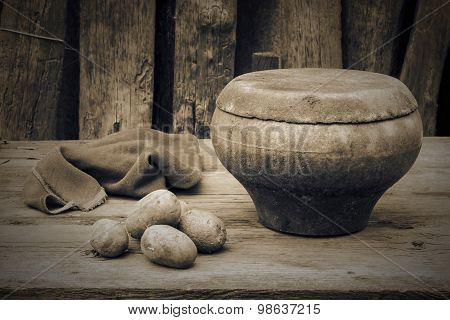 Old Cast Iron Pot, Rag And Potatoes On The Old Table Near The Fence