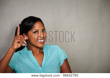 Charismatic Woman Pointing Up While Smiling