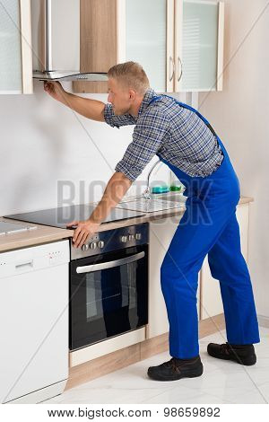Young Handyman In Overall Fixing Kitchen Extractor Fan In Kitchen poster