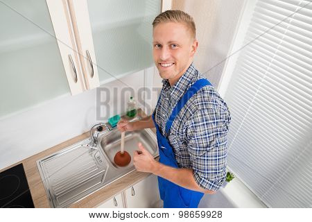 Plumber With Plunger In Kitchen