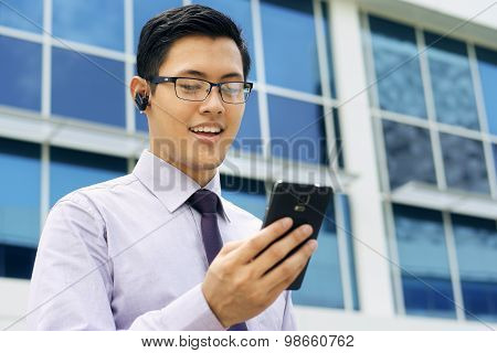 Businessman Talking Video Call On Mobile With Wireless Handsfree