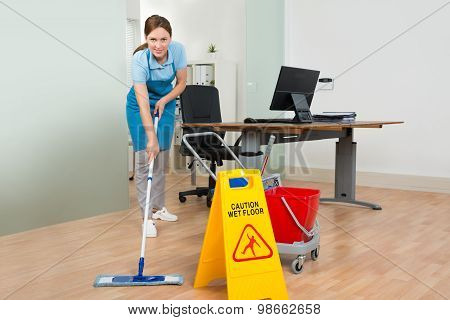 Female Janitor Cleaning Hardwood Floor In Office
