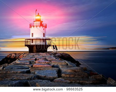 Lighthouse on top of a rocky island slow exposure with added lens flare