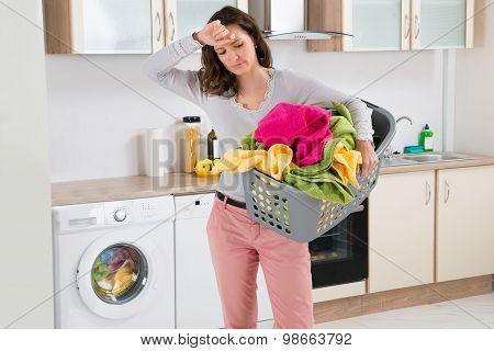 Young Tired Woman Carrying Basket With Clothes In Kitchen Room poster