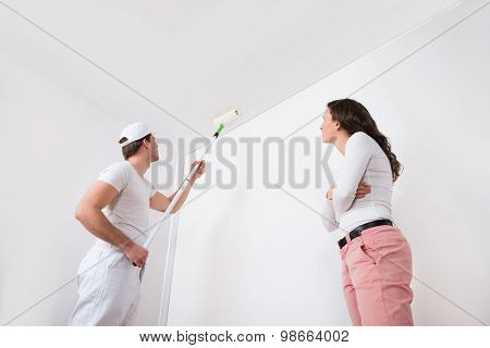 Young Woman Looking At Painter Painting White On Wall In House poster