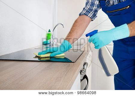 Worker Cleaning Electric Hob