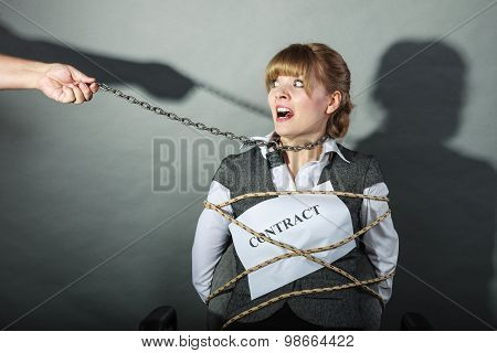 Scared businesswoman bound by contract terms and conditions. Afraid and helpless woman tied to chair become slave. Human hand hold chain and has power over girl. Business and law concept. poster