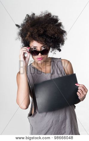 Hispanic brunette rebel model with afro like hair wearing grey sleeveless shirt and pulling down sunglasses holding blank board mugshot concept. poster