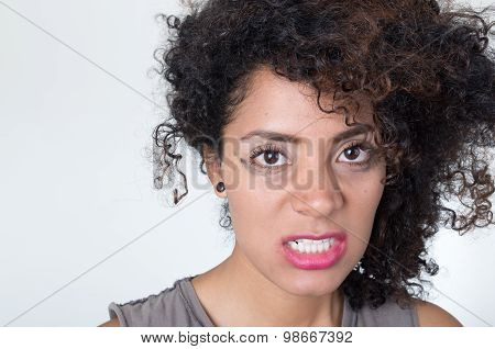 Headshot hispanic brunette model with messy makeup and hair looking angrily into camera, white backg