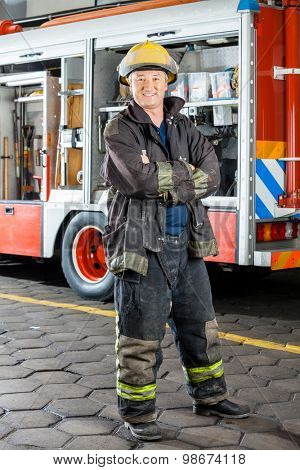Portrait of happy fireman standing arms crossed against truck at fire station