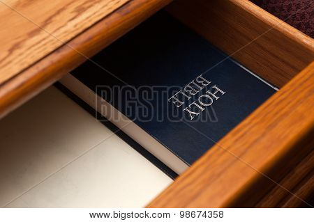 Holy Bible book in a open drawer upside down