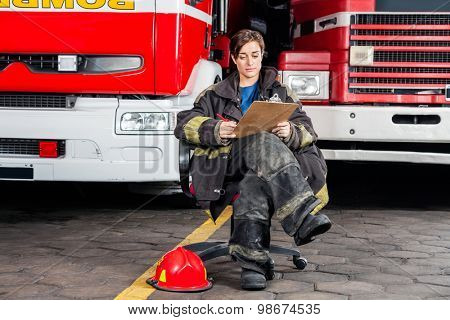 Full length young firewoman writing on clipboard while sitting against trucks at fire station