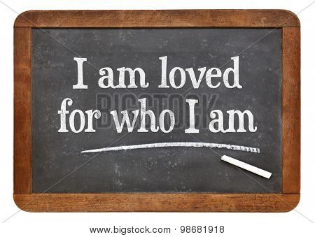 I am loved for who I am - positive affirmation words on a vintage slate blackboard
