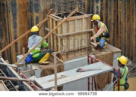 Construction workers installing pile cap and stump formwork