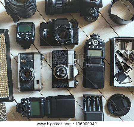 Vintage Film And DSLR Camera Photo Accessories On White Wooden Background Technology Development Concept. Top View