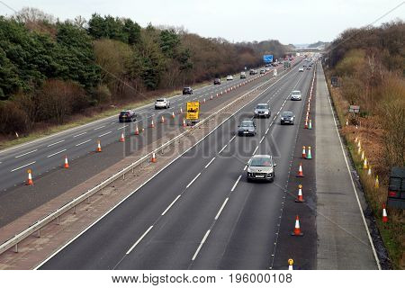 Fleet, Hampshire, Uk - March 11Th 2017: View From A Motorway Bridge Of Traffic Driving Through Cones