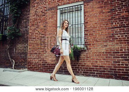 Beautiful young adult happy student woman walking at university campus to study wearing white sexy dress.