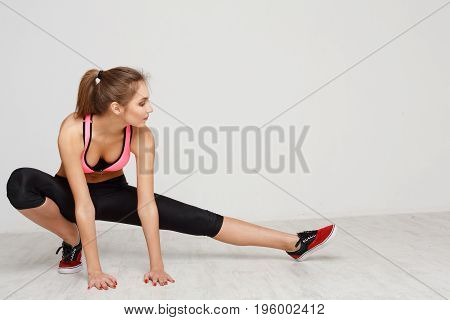 Fitness woman at stretching training at white background indoors. Young slim girl makes aerobics exercise.