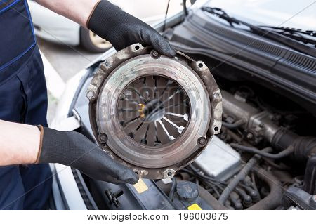 Auto mechanic wearing protective work gloves holds old clutch basket over a car engine