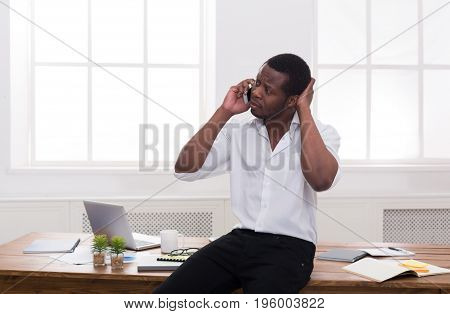 Business call. Young african-american businessman in white has mobile phone talk in modern white office interior.