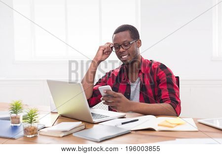 Happy african-american businessman in office, texting on phone while working on laptop