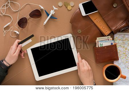 Booking tickets online by tablet and credit card top view. Preparing for vacation, travel and modern technologies concept. Holding device with blank screen, mockup