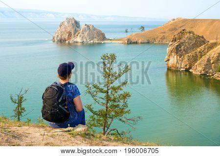 Lake Baikal, Siberia, Russia. A woman backpacker looks at the Shamanka Rock, Cape Burhan on Olkhon Island