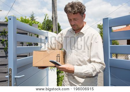 Delivery Man With Cap And Cardboard In Hands, Searching The Address On The Mobile Phone