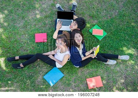 Young Students Group Smiling with Folders Book and Laptop computer Smiling on Grass in Education Campus University Top view